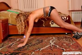 Blonde sports girl stretches in tights at home