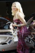 Gwen Stefani shows off her breast implants wearing a strapless dress outside a f