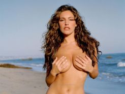 Kelly Brook showing her naked but covered body at the beach for Alan Strutt phot