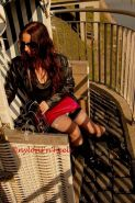 Redhead Justine in nylons and boots having a smoke