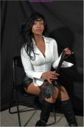 Pantyless ebony femdom puts on a pair of buttery leather gloves and then bends o