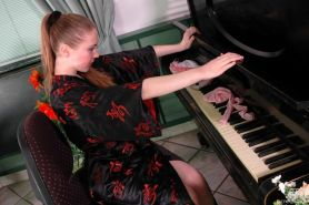 Young piano player in her fine pink lingerie and nylons