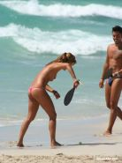 Voyeur shots of a cute topless girl playing at the beach
