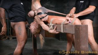 Wenona is blindfolded, gagged, bent over and bound to a wooden frame. a position