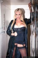 Blonde in a sexy corset and stockingsunder her long leather coat