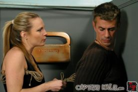 Mistress Harmony gives wall bound male CBT treatment and strapon