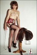 Latex and stockings long legs dominatrix posing with riding whip