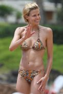 Brooke Burns in bikini paddle surfing on a Hawaiian beach