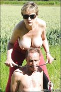 Topless mature femdom in red tights torturing male pets cock out