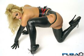 Sexy blonde milf, Shyla Stylez, is wrapped in a latex corset and boots and bound