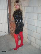 Fetish wife wearing tight latex catsuit and red heeld boots