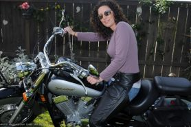 Fortyish biker babe strips next to her big chrome motorcycle