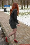 Redhead Justine with sexy stockinged legs in red high heels