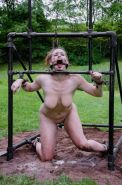 Bella Rossi is chain bound outdoors in the mud made to suck masters cock