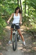 Nude girl bicycling outdoors