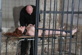 Beautiful red haired amateur subbie is chained up in a jail cell