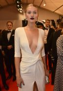 Toni Garrn flaunting her boobs braless in a low cut and high slit white dress at