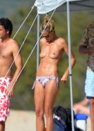 Heidi Klum tanning topless on a sandy beach in Corsica