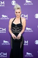 Kaley Cuoco shows cleavage wearing a low cut black dress at 48th Annual Academy