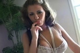 A smokin gal bedecked in pearls emits smoke curls into the air around her as she