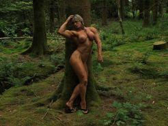 sexy female bodybuilder posing naked in forest