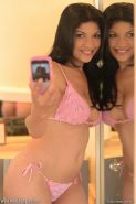 Natalia Spice has fun with her camera phone before taking off her lacy lingerie and masturbating