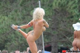 Hot strippers showing off for the people at an outdoor public nudity party