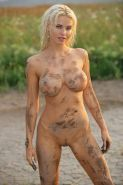 Busty blonde babe Kathy gets all muddy in the Amazon