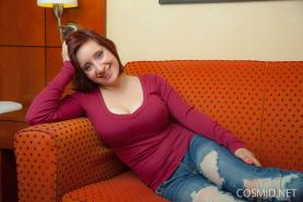 Busty redhead Chelsea Bell strips naked for you on the couch