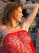 Hot redhead Maria D shows off her big boobs outside on a beach