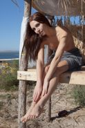 Gemma's natural beauty, carefree allure, and spontaneous personality stand out as she happily hangs out and poses in a shack by the beach.