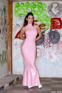 Pics of Ryan Keely in a classic pink latex gown in a dirty room with graffiti all over the walls