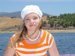 Blonde teen Little April playing with her private parts on a lake