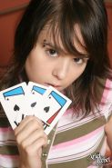 Pictures of teen Ariel Rebel playing a game of cards in bed