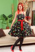 Beuatiful redhead in a black and red summer dress and black stockings.