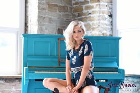 Jess Davies teasing at the piano in her cute blue outfit