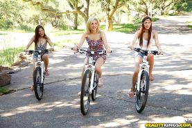 Three sexy girls ride bikes in the park naked and then get it on