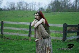 Liz Vicious strips slowly on a farm